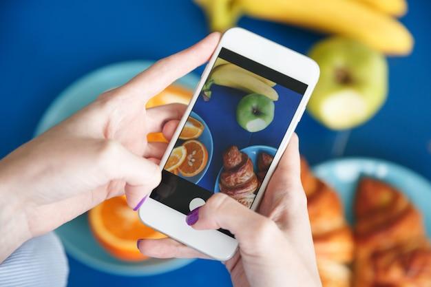 女性の手が食べ物で携帯電話で写真を撮る 無料写真