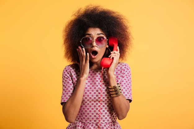 レトロな電話を保持しているアフロの髪型とショックを受けたレトロな女の子のクローズアップ写真 無料写真