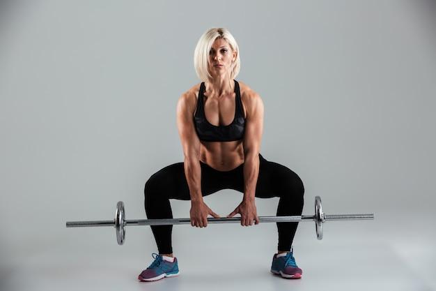 スクワットをして自信を持って筋肉の大人のスポーツウーマンの肖像画 無料写真