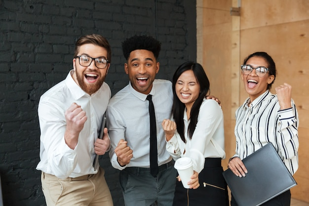 幸せな興奮して若いビジネス部門の同僚は、勝者のジェスチャーを作ります。 無料写真