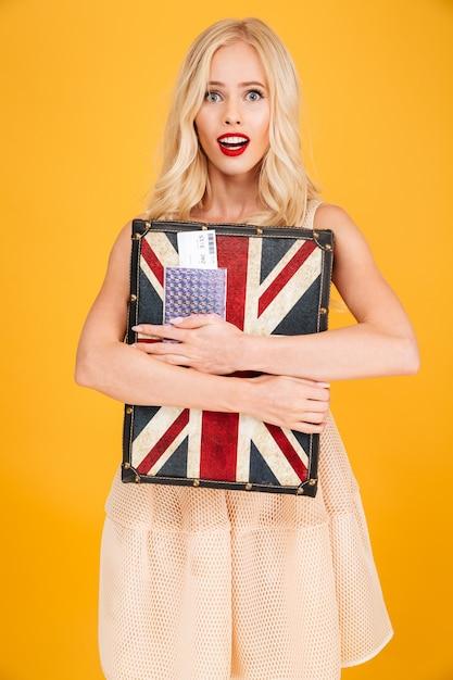 英国のプリントスーツケースを持ってショックを受けた若いブロンドの女性 無料写真