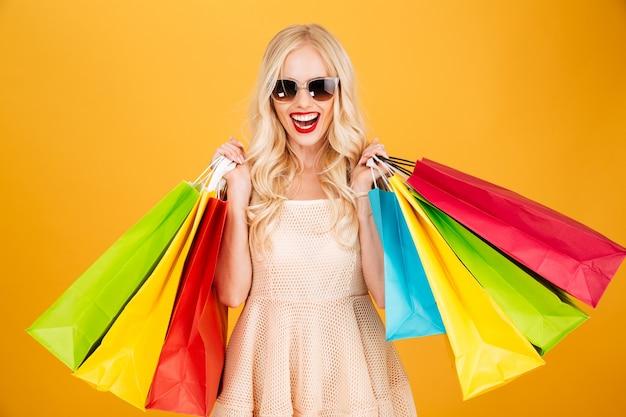 買い物袋を保持している笑顔の若いブロンドの女性。 無料写真
