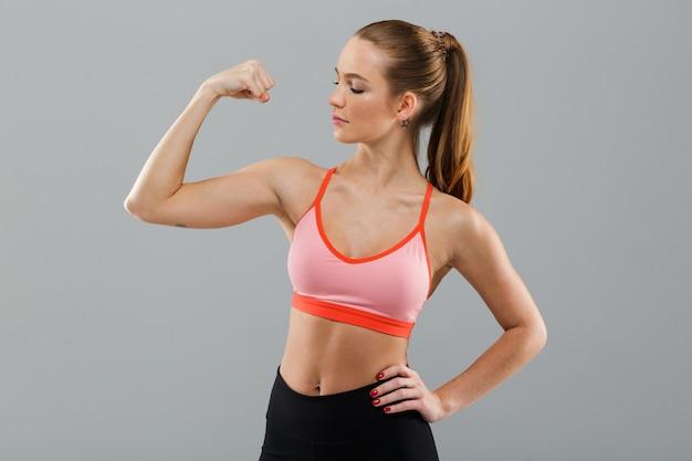 Удивительная молодая спортивная женщина, показывающая бицепс. Бесплатные Фотографии