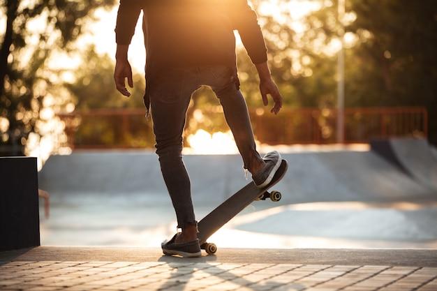 Молодой африканский человек делает скейтбординг на открытом воздухе Бесплатные Фотографии