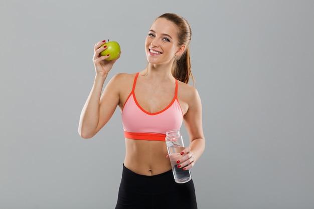 Портрет улыбающегося здоровая спортивная девушка держит зеленое яблоко Бесплатные Фотографии