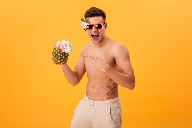 Веселый голый мужчина в шортах и необычных очках держит коктейль, указывая на него и глядя на камеру над желтым Бесплатные Фотографии