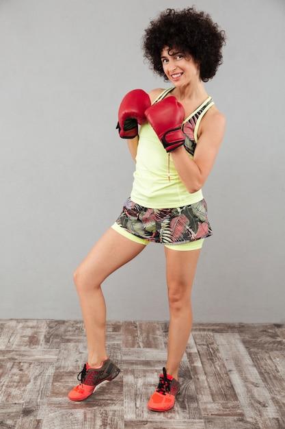 ボクシンググローブで笑顔のスポーツ女性の完全な長さの画像 無料写真
