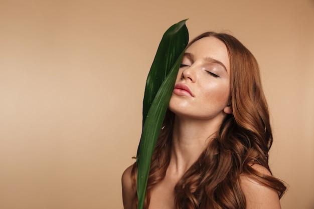 Портрет красоты рыжая женщина с длинными волосами позирует с зелеными листьями Бесплатные Фотографии