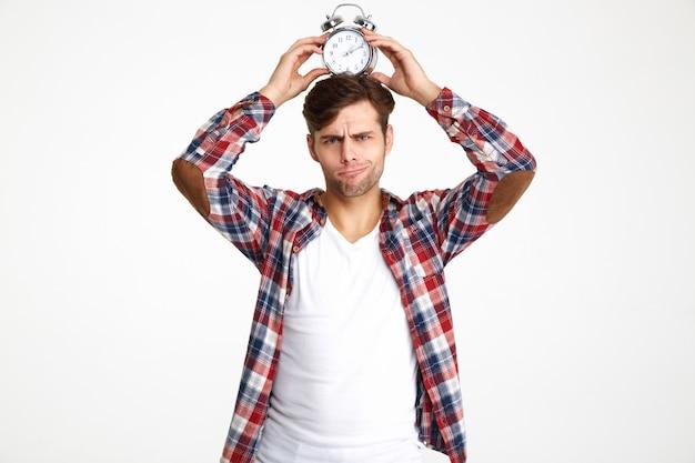 目覚まし時計を保持している面白い若者の肖像 無料写真