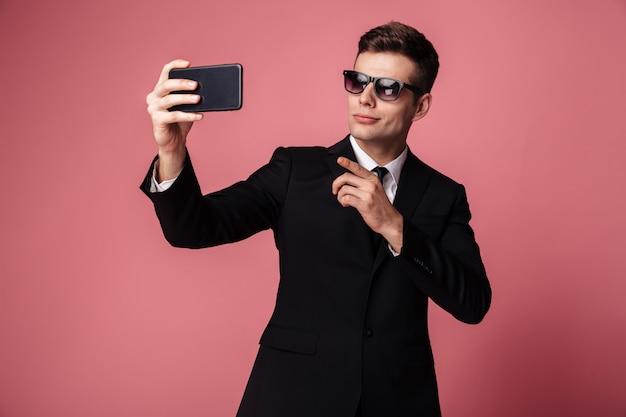 Сконцентрированный молодой бизнесмен делает селфи по мобильному телефону. Бесплатные Фотографии