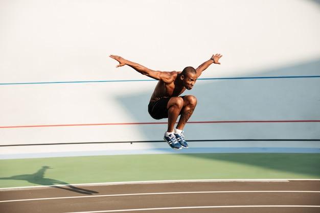半分裸の強いフィットアフリカのスポーツマンのジャンプの肖像画 無料写真