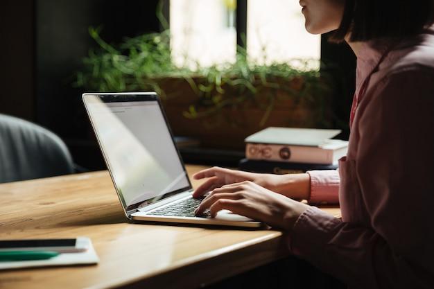 Брюнетка женщина сидит за столом Бесплатные Фотографии