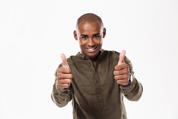Улыбающийся африканский человек показывает палец вверх и смотрит Бесплатные Фотографии