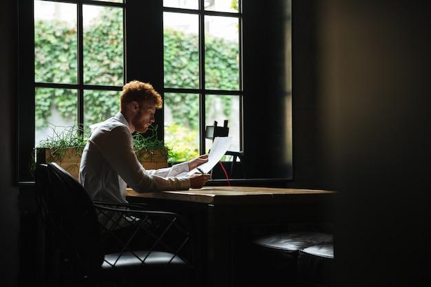 カフェテリアに座って、契約書を読んでひげを生やした実業家のひげを生やした集中リードヘッドの写真 無料写真