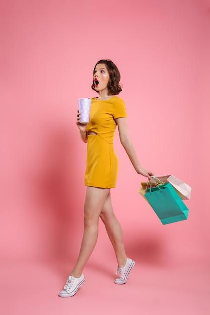 飲み物とカラフルなショッピングバッグを持って、よそ見黄色のドレスでかわいい驚かれる女性の完全な長さの写真 無料写真