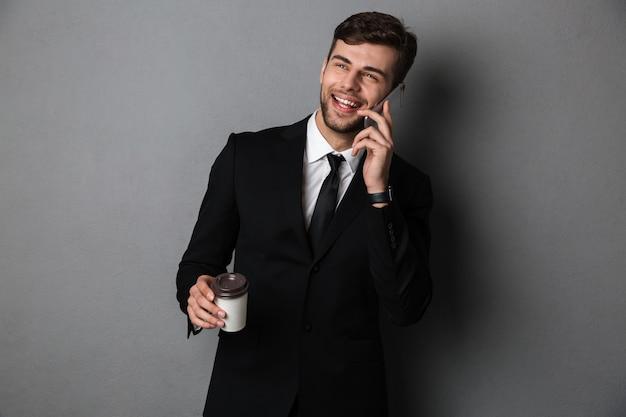 Молодой успешный деловой человек разговаривает по мобильному телефону, держа чашку кофе, глядя в сторону Бесплатные Фотографии
