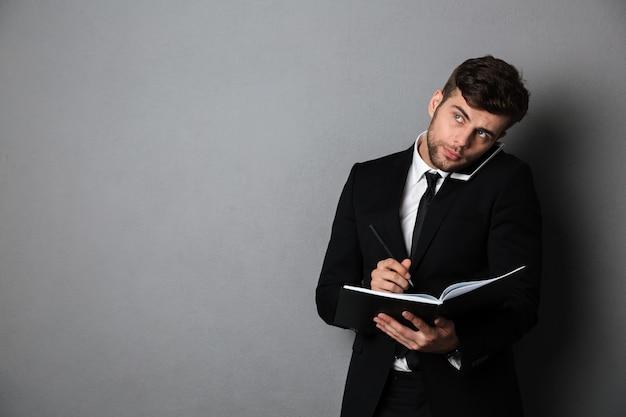 Красивый мышления бизнесмен заметок во время разговора по мобильному телефону, глядя в сторону Бесплатные Фотографии