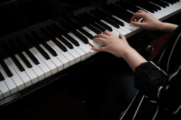 美しいアジアの女の子はピアノを弾くことを学ぶ。 Premium写真