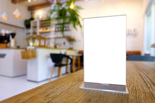バーレストランカフェの木のテーブルの上に立っているメニューフレームをモックアップします。テキスト用のスペース Premium写真