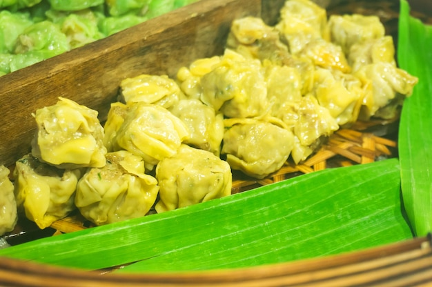 中国の蒸し餃子、竹の蒸し蒸し蒸し。屋台の食べ物。選択的に焦点を合わせる。 Premium写真