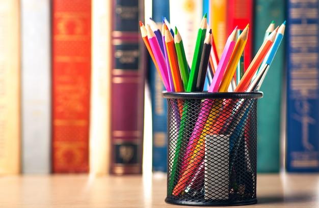 Цветные карандаши в пенале на книжной полке Premium Фотографии