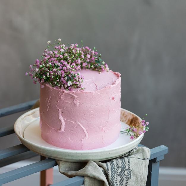 Фон с розовым кремовым тортом, украшенным мелкими цветами, серой скатертью и столом в скандинавском стиле Premium Фотографии