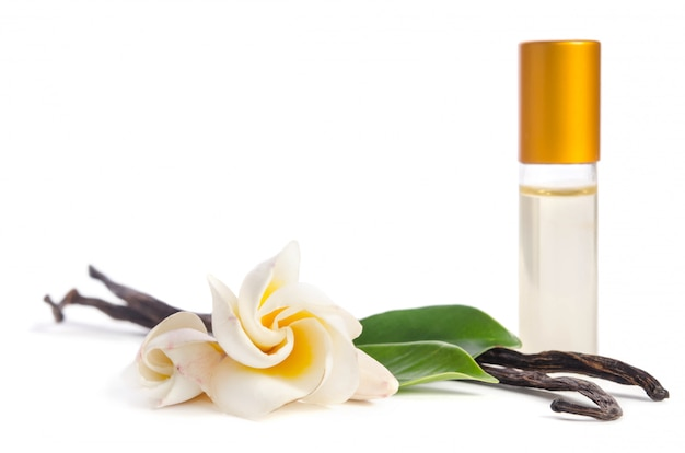 Красивые цветы, натуральная ваниль и бутылки с маслами для кожи, изолированные на белом Premium Фотографии
