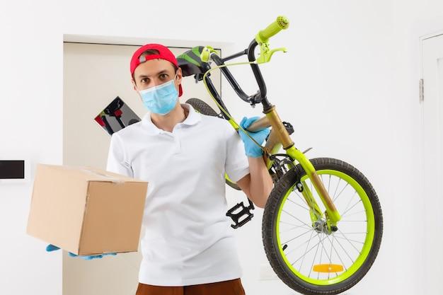 防護マスクの男が自転車で食べ物を届けています Premium写真