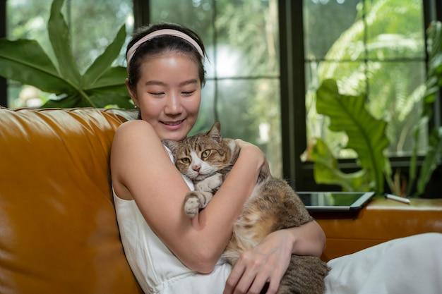Азиатская женщина и кошка на диване Premium Фотографии