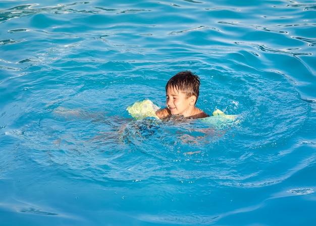 Маленький мальчик учится плавать в бассейне Premium Фотографии