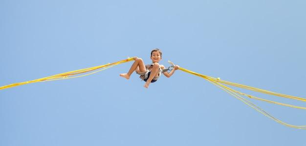 Мальчик прыгает на батуте Premium Фотографии