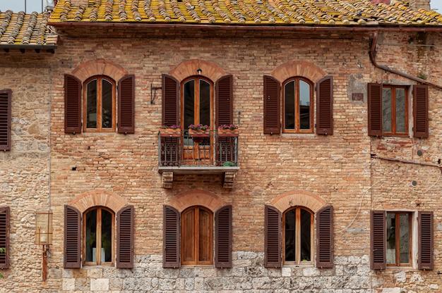 古い赤レンガの建物の窓と瓦の屋根に開いている木製シャッター Premium写真