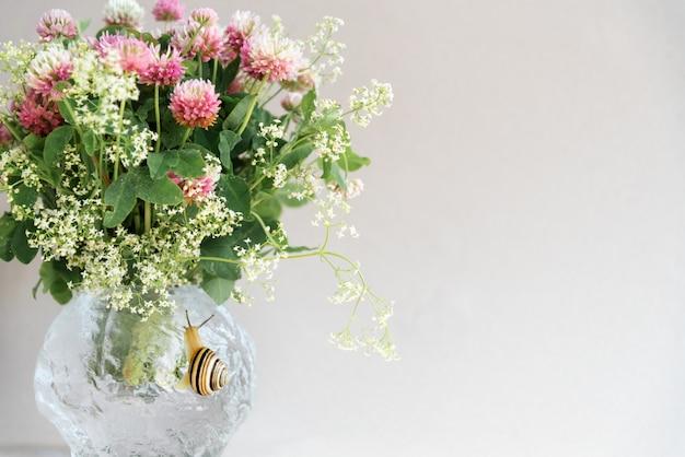ピンクのクローバーの花とかわいいカタツムリの丸い花瓶 Premium写真