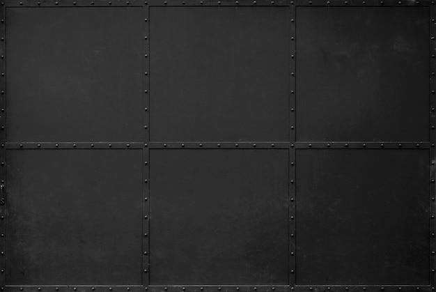暗い黒い金属のテクスチャ背景。倉庫のドアは黒鉄のドアです。 Premium写真