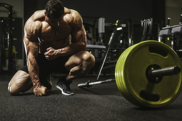 筋肉トレーニングボディービル概念を汲み上げるハンサムな強い運動男性 Premium写真
