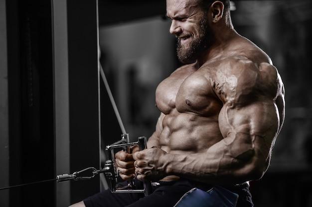 ジムの裸の胴体でプルアップ運動を行う筋肉ボディービルダーフィットネス男性。背中の筋肉トレーニングフィットネスとボディービルの概念の背景を汲み上げるハンサムな強い運動男性。 Premium写真