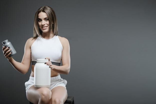 サプリメントホエイプロテインシェークパウダーを持つ少女 Premium写真