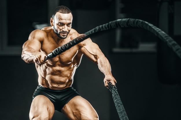 バトルロープを使用してトレーニングフィットネス選手 Premium写真