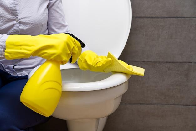 Женщина, уборка туалета. домохозяйка, чистящая туалет или туалет, чистит туалет Premium Фотографии
