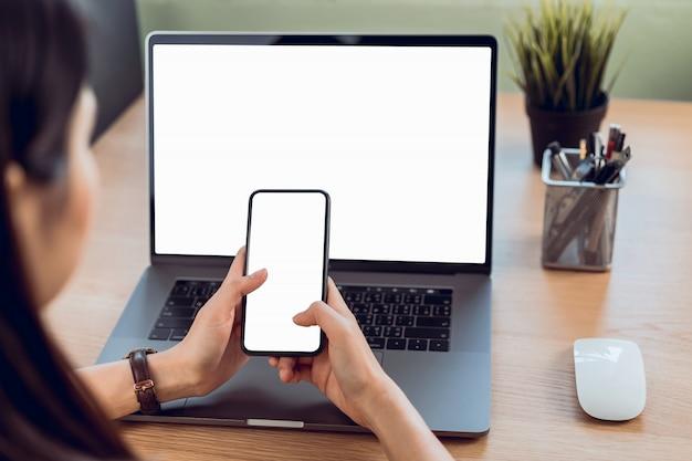 空白のコピースペース画面を持つスマートフォンを持つ女性の手 Premium写真