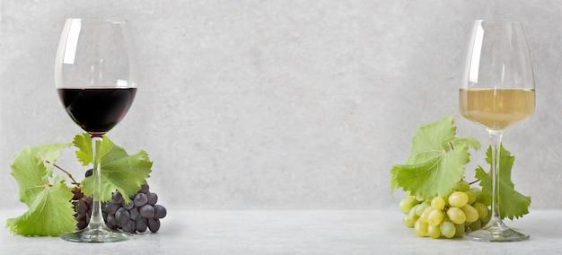 Стакан с красным вином и стакан с белым вином. светло-серый фон. Premium Фотографии
