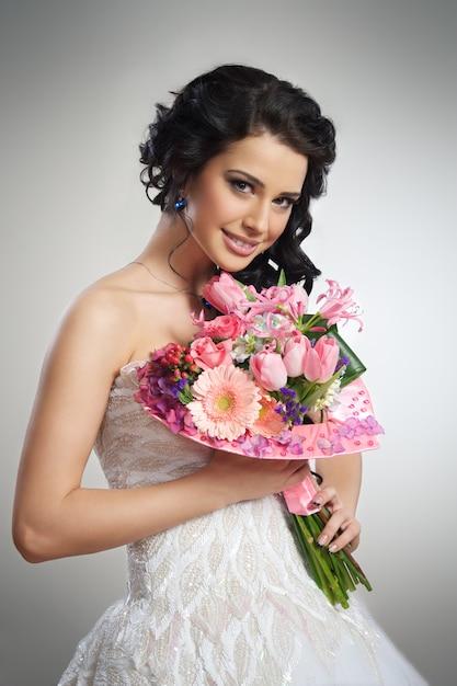 Красивая девушка в белом свадебном платье с букетом цветов Premium Фотографии