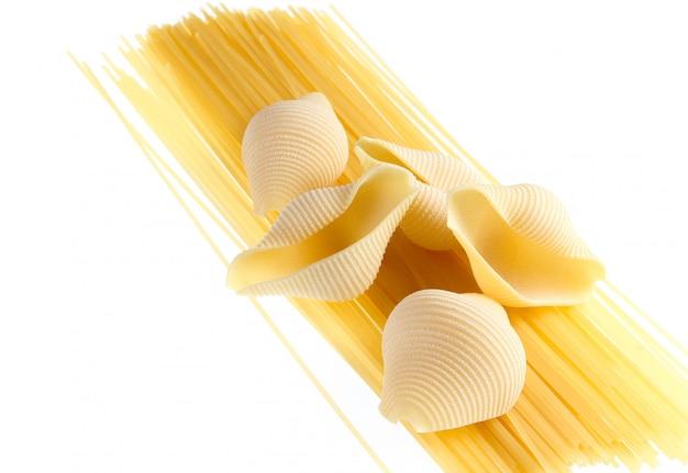 生の乾燥コンキリオーニ、イタリアのパスタをクローズアップで分離白 Premium写真