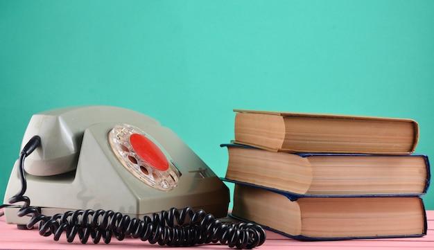 Ретро роторный телефон, стопка книг на столе, изолированных на фоне зеленой пастельной стены Premium Фотографии