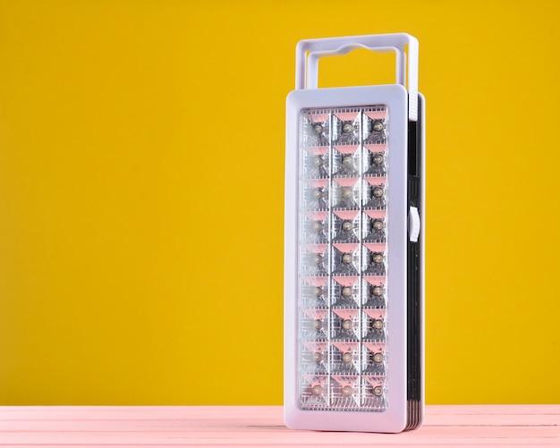 プラスチックは、黄色の背景に懐中電灯を主導 Premium写真
