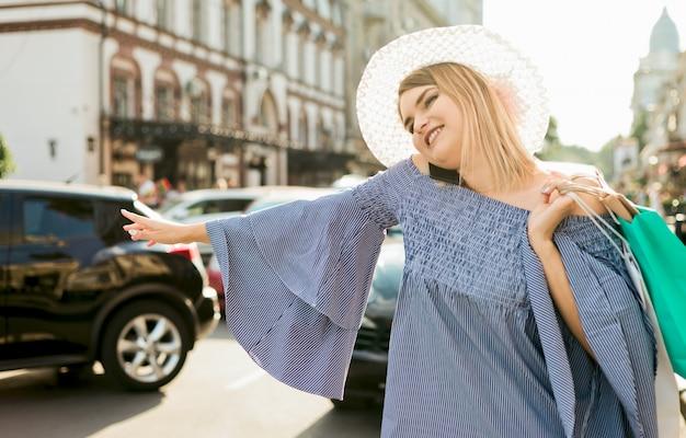 若い女性のジェスチャーで車をキャッチし、市内の道路で電話で話しています。ヒッチハイクのコンセプト Premium写真