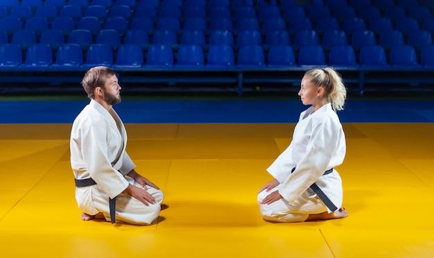 Боевые искусства. щадящие портнеры. спорт мужчина и женщина приветствуют друг друга, сидя в спортивном зале Premium Фотографии