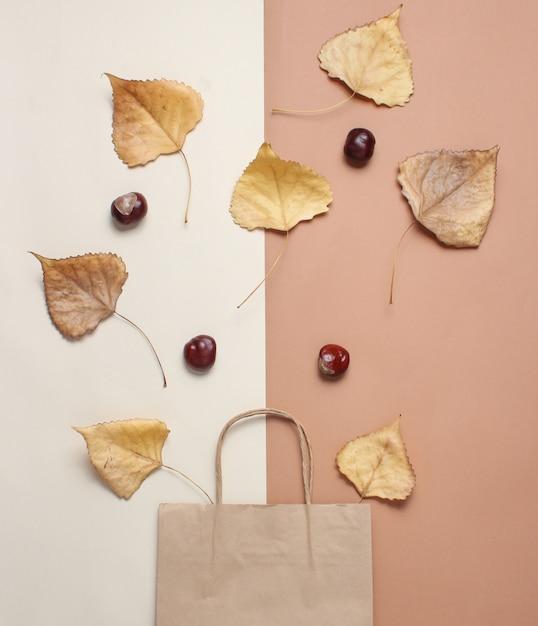 Бумажный пакет для покупок, опавшие осенние листья на бежево-коричневом столе. осенние покупки, продажа, вид сверху, минимализм Premium Фотографии