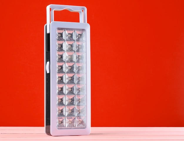 プラスチック製の赤い背景の懐中電灯 Premium写真