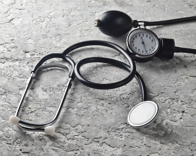 Медицинский инструмент для измерения давления. стетоскоп на сером бетонном столе. сердечно-сосудистая диагностика. Premium Фотографии